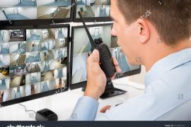 stock-photo-close-up-of-male-security-guard-talking-on-walkie-talkie-while-monitoring-multiple-cctv-footage-471492710