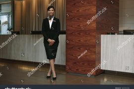 stock-photo-full-length-portrait-of-female-hotel-receptionist-standing-at-workplace-beautiful-woman-1069956038
